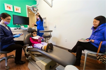 Dr. Ciano of Montgomery Pediatric Dentistry explains a dental procedure to her pediatric patient