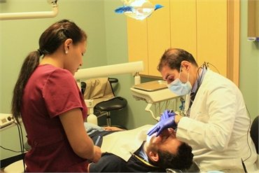 Dr. Uthman performing periodontal procedure