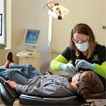 Dental Hygienist at Harmony Dental examining patient