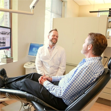 Eugene dentist Dr. Umberger chatting with dental implants patient