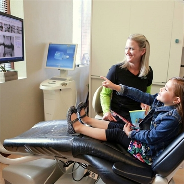 Dental Hygienist explains root canal therapy to child patient at Harmony Dental