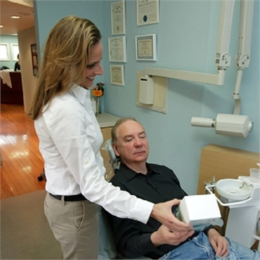 Dental hygienist explains teeth whitening options at the office of Rolando Cibischino DMD