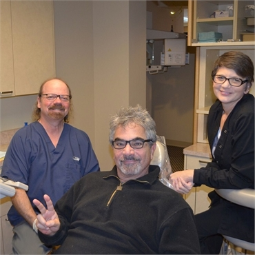 Happy root canal patient with Dr. Hickey and dental hygienist at Sound to Mountain Dental Health Cen