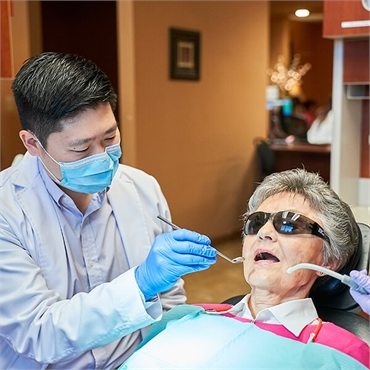 Renton dentist Dr Hu with an elderly patient at Hu Smiles in Renton