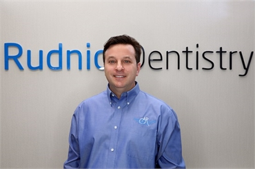 Palm Beach Gardens FL Dentist Andrew Rudnick DMD in front of sign