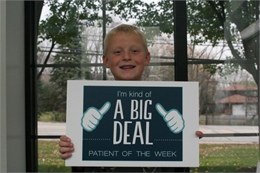 Young patient posing with sign at Gurnee IL dentist Bradley Rule DDS