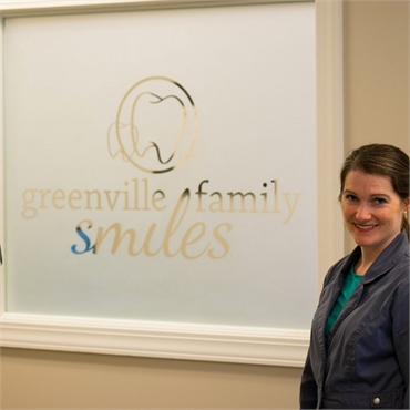 Greenville dentist Anna Goldston standing in front of the signage at Greenville Family Smiles